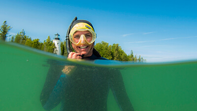 A snorkeler smiles with a lighthouse in the background