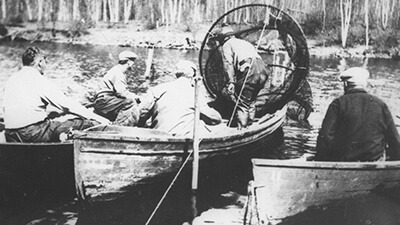 Black and white photo of people fishing from canoes